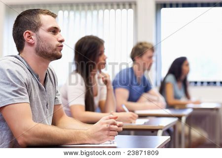 Handsome young man listening in a classroom