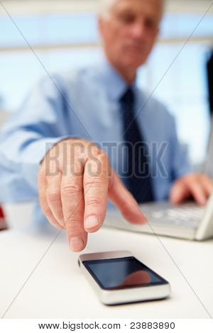 Senior businessman with laptop and phone