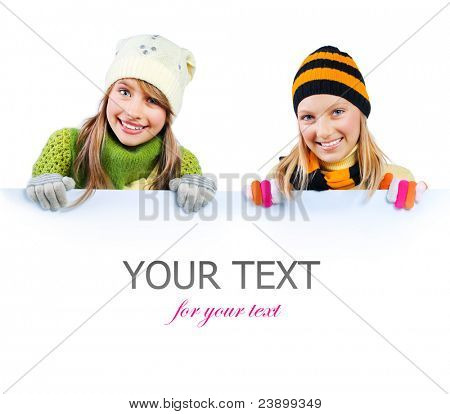 Beautiful Girls peeking from behind blank sign billboard. Space for Your Text