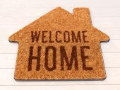 Brown House Icon Shape Coir Doormat With Text Print Welcome Home On Wooden Floor. 3d Illustration poster