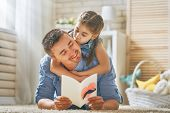 Happy fathers day! Child daughter congratulating dad and giving him postcard. Daddy and girl smilin poster