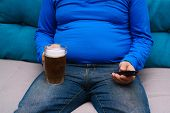 Beer Belly, Overweight. Man With Obese Abdomen Sitting Om The Coach With Tv Remote And Mug Of Beer,  poster