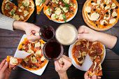 Friends Eating Pizza. Top View On Male Hands Clinking Mugs With Beer Over Table With Many Pizzas. Pa poster