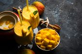 Mango Lassi Or Smoothie In Big Glass Or Small Bottles With Curd, Cut Fruit Pieces And Blender. Moody poster