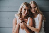 Blonde Cute Girl Hugs Blonde Mother On Wooden Background. Concept Of Relationship Between Mother And poster