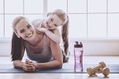 Beautiful Young Woman And Charming Little Girl Are Looking At Camera And Smiling While Lying On Yoga poster