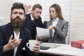 Man With Beard On Hopeful Face Holds Mug, Bosses, Coworkers, Colleagues On Background. Business Nego poster