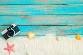 Summer Background -   Top View Of Beach Sand With Retro Camera, Starfish And Shells On Blue Wooden B poster