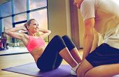 fitness, sport, training, gym and lifestyle concept - woman with personal trainer doing sit ups in g poster