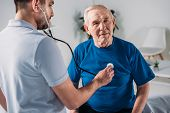 Rehabilitation Therapist With Stethoscope Checking Senior Mans Heartbeat poster