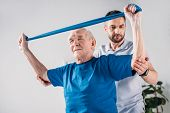 Focused Rehabilitation Therapist Assisting Senior Man Exercising With Rubber Tape poster