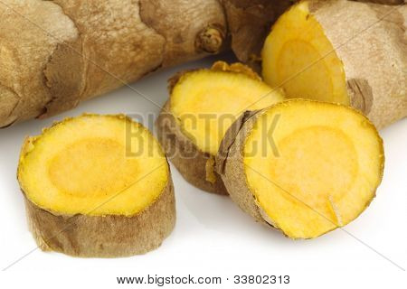 turmeric(Curcuma longa) root and some cut pieces on a white background