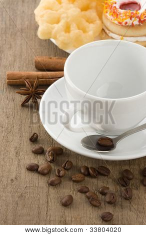 cup of coffee with beans and cakes on wood board