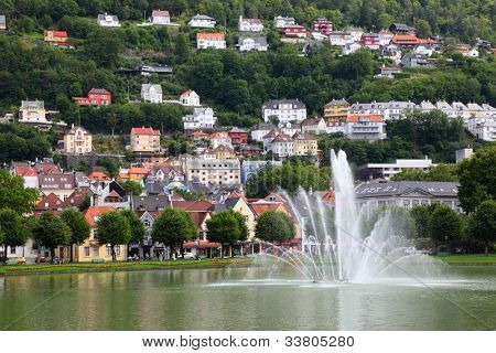 Houses and green trees in small town under mountain with fountain at foreground