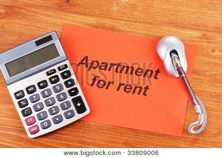 inserieren mieten Apartmennt auf rotes Papier auf Holz Hintergrund close up