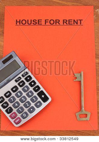 Inserieren Sie Vermietung Häuser auf rotes Papier auf Holz Hintergrund