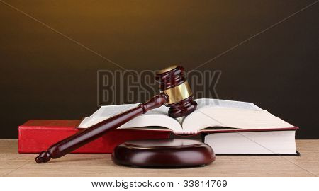 Judge's gavel and books on wooden table on brown background