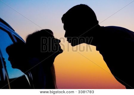 Two Silhouettes Of Kissing People On Sunset Background
