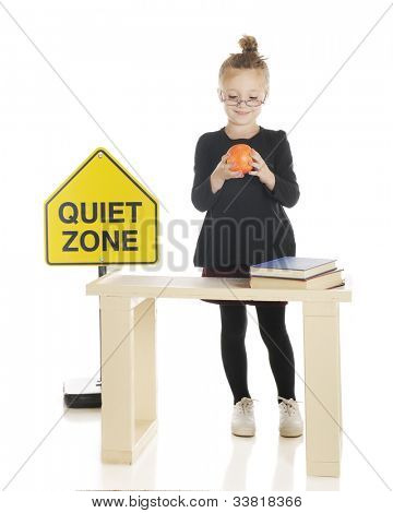 An adorable girl playing teacher.  She's admiring an apple as she stands behind her desk.  On a white background.