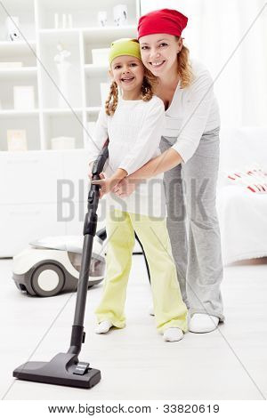 Little girl learning the household - vacuum cleaning together with mother