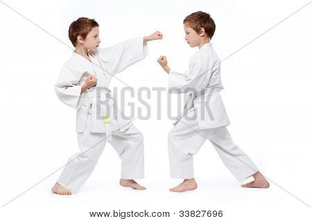 Little twins in uniform practicing judo, isolated on white