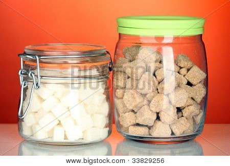 Jar with brown cane sugar lump and sugar-bowl with white lump sugar isolated on white
