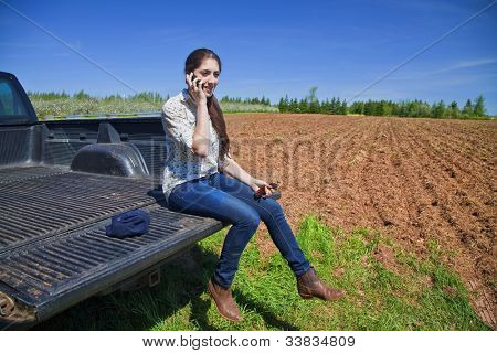 Young woman farmer sitting on the tail board of her truck and speaking on her phone.