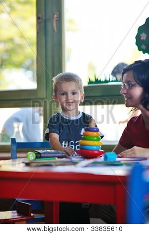 happy little child play game and have fun, education lessons in colorful kinder garden playground indoors