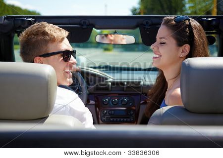 Young guy and girl sit in a cabriolet, look at each other and laugh, back view