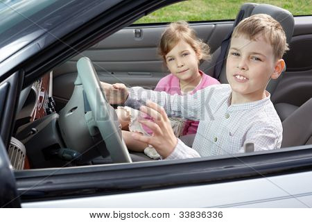 A boy sits on a driver seat in the open top car and his sister sits on a passenger seat, both look into a camera, close-up.