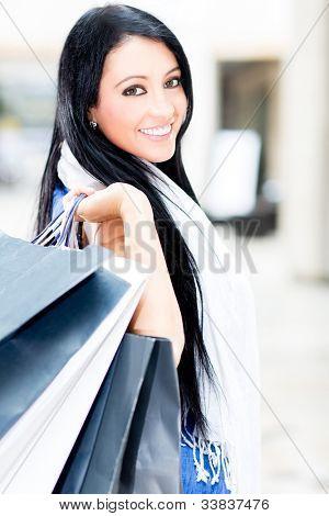 Bela mulher compra segurando sacos no shopping