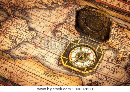 Vintage pirate retro compass on ancient world map. The map used for background is in Public domain. Map source: Library of Congress. Country: Belgium Year: 1570. Author: Abraham Ortelius (1527-1598)
