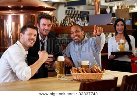 Happy friends having leisure in pub watching sport in TV together drinking beer cheering for team.