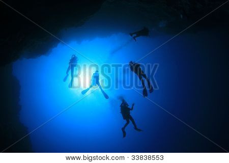 Underwater Group of Scuba Divers silhouetted against sun