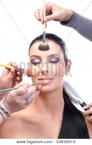 Makeup artists working on beautiful female model simultaneously, applying makeup by brush, combing hair, applying lipstick.