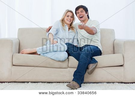 A young couple are sitting down on a couch looking at the camera and laughing