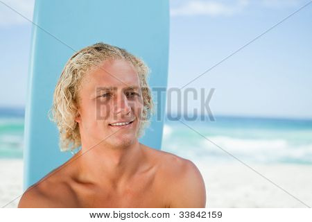 Young blonde man sitting on the beach with his surfboard while showing a smile
