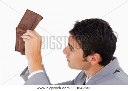 Man in a suit looking in his empty wallet against white background