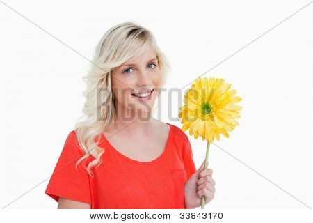 Smiling young woman holding a yellow flower against a white background