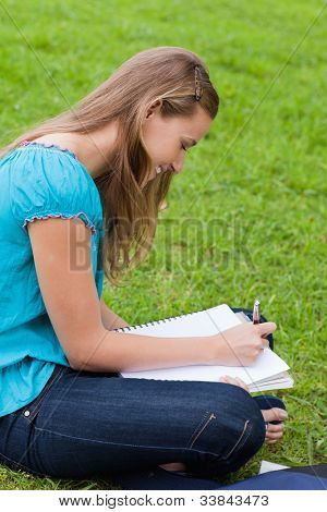 Young happy girl doing her homework while sitting on the grass in the countryside