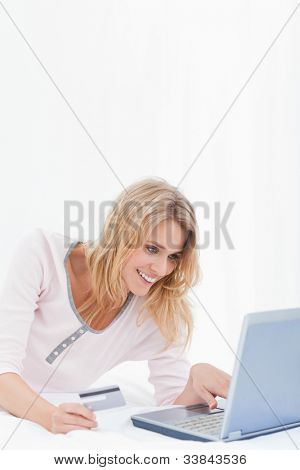 A woman lying on her bed is smiling as she is ordering items online with her credit card and laptop