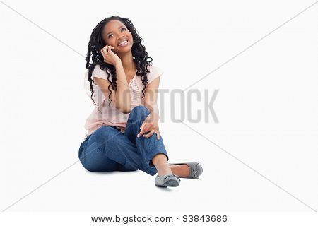 A smiling woman sitting on the floor is talking on her mobile phone and looking up against a white background