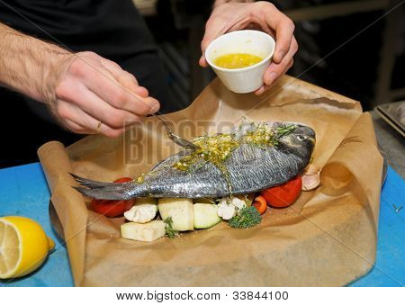 Chef is cooking dorade with vegetables