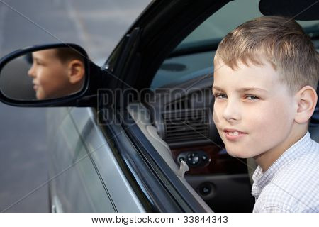 A boy sits half-turned back on a driver place in a open top car