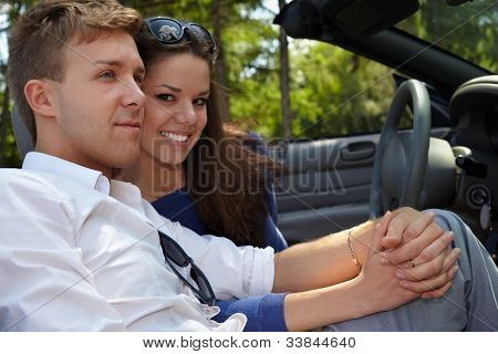 Young couple sits in a car, nestling their cheeks and holding hand in hand