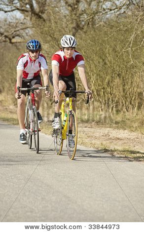 Two active male athletes riding cycles in a rural area