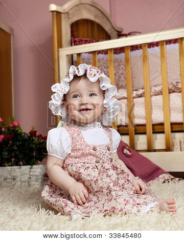 little child baby girl in dress sitting on the floor indoors in babyroom smiling happy