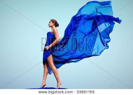 Photo of graceful female folded in dark blue chiffon shawl outside