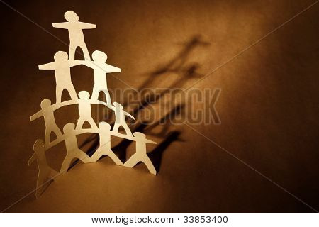 Human team pyramid on brown background