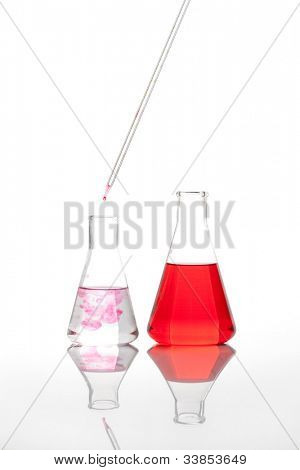 Two laboratory flasks - Clear liquid mixed with a red colored chemical reagent, isolated
